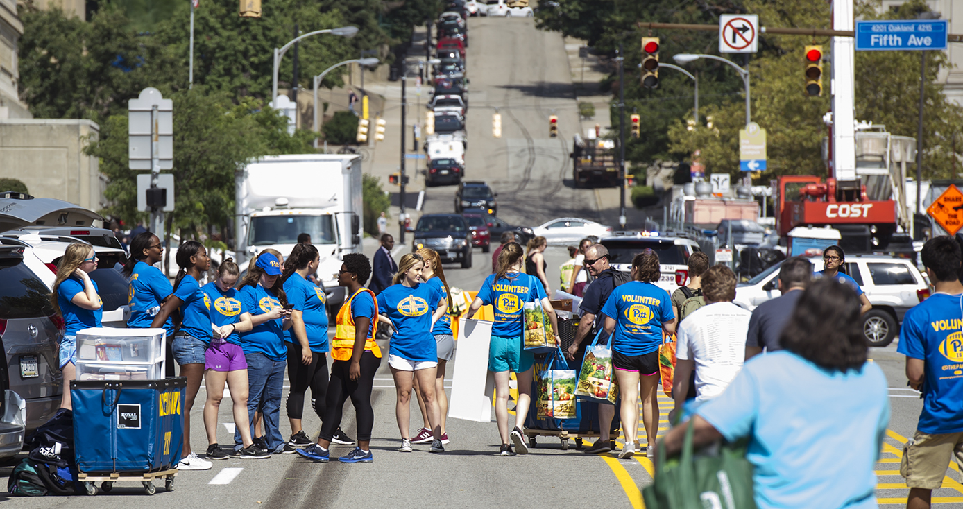 Large group of students in Pitt T-shirts gathered on streets closed to traffic for move-in day on the Pittsburgh campus