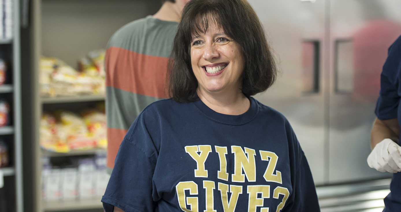 "woman in blue and gold ""Yinz Give?"" shirt"