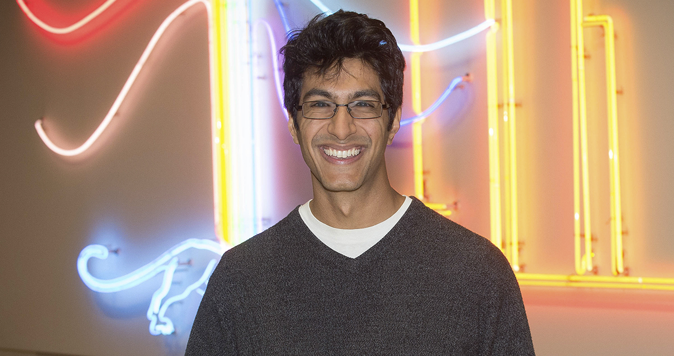 Samir Lakhani standing in front of a colorful neon wall display