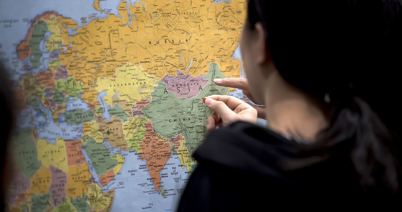 A person in black puts a mark on a map of the world