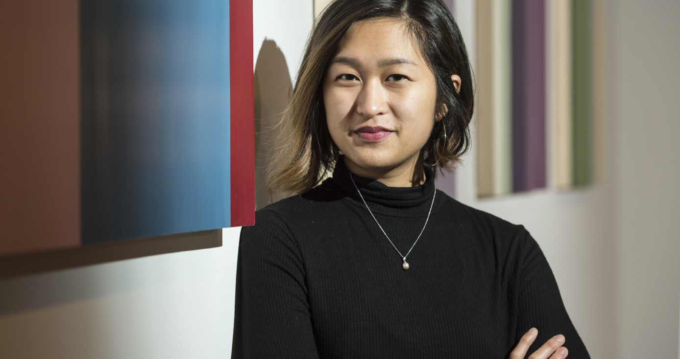 Pearl Galido headshot, wearing black mockneck top and necklace against a background with multi-color stripes
