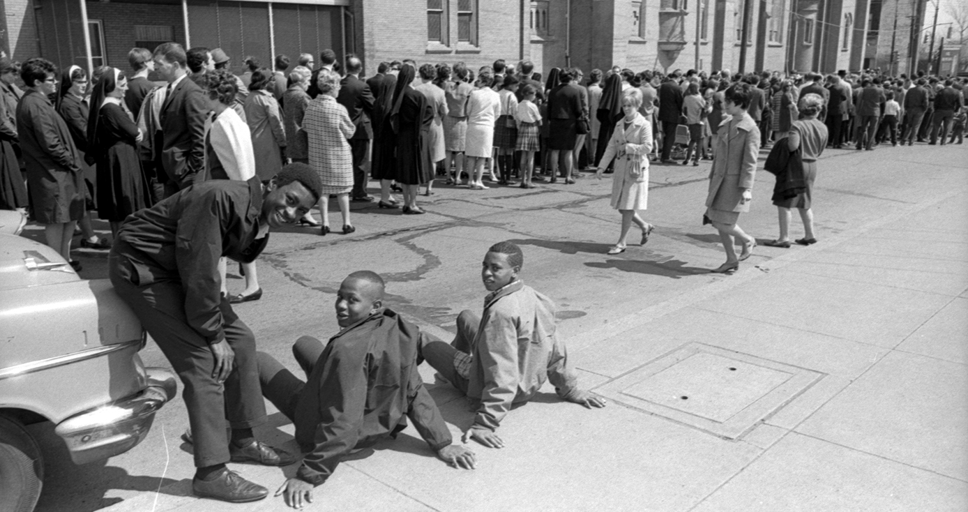 crowd of people gathered on street/sidewalk near a church with three boys in the foreground on National Day of Mourning following Martin Luther King Jr.'s assassination in 1968.