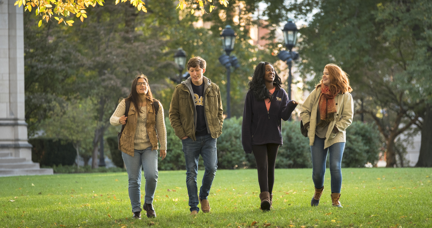 four students walking on Pitt campus in fall