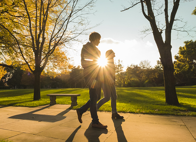 two people walking on campus with the sun behind them