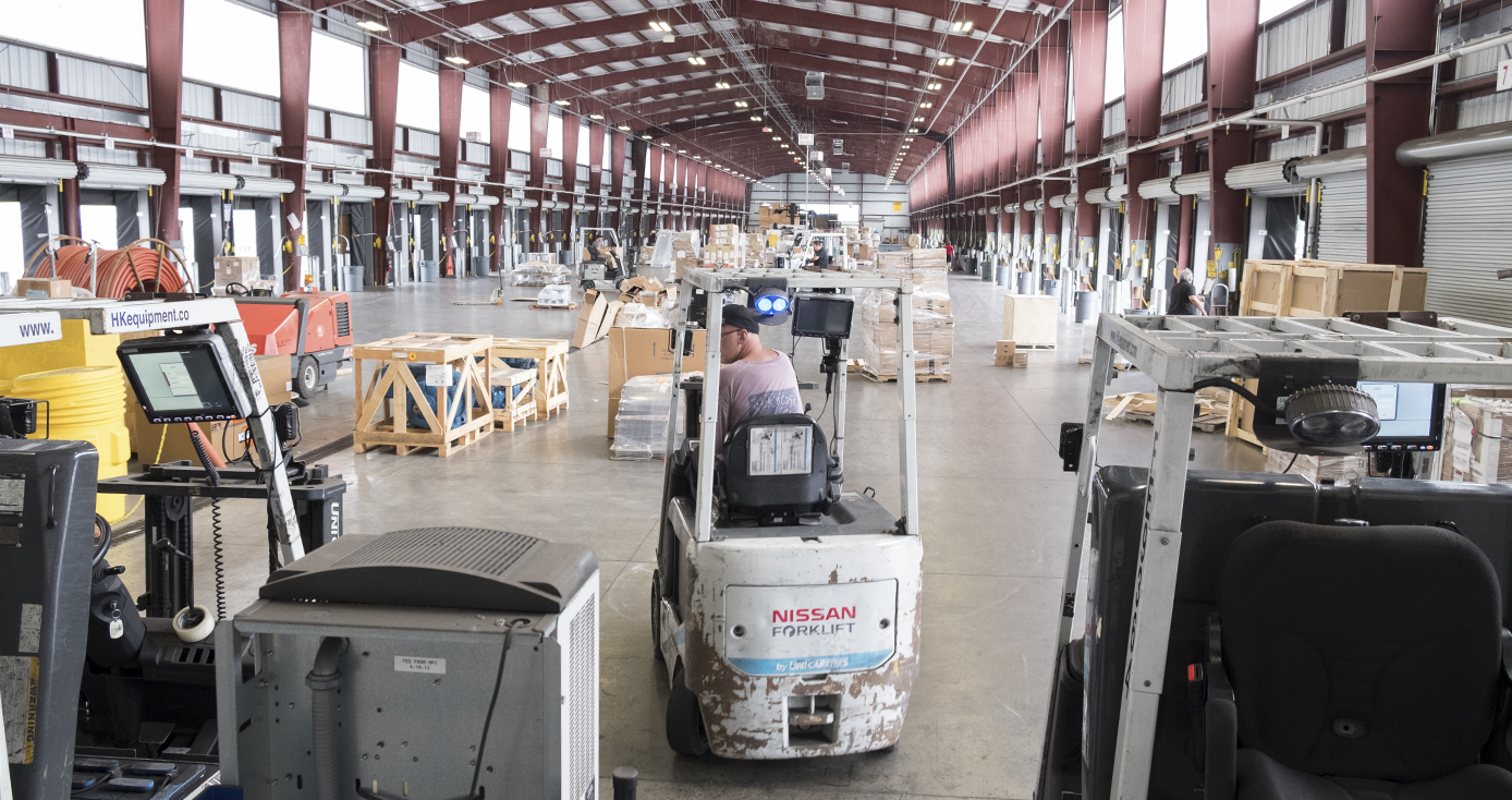 Interior of trucking facility including man operating a forklift