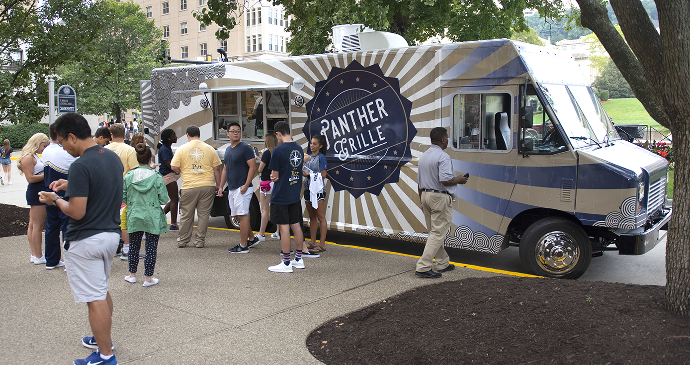 Panther Grille food truck parked among trees with a group of people waiting to order