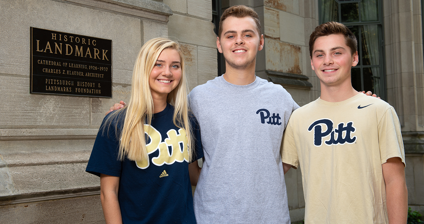 the triplets together in Pitt shirts before the Cathedral