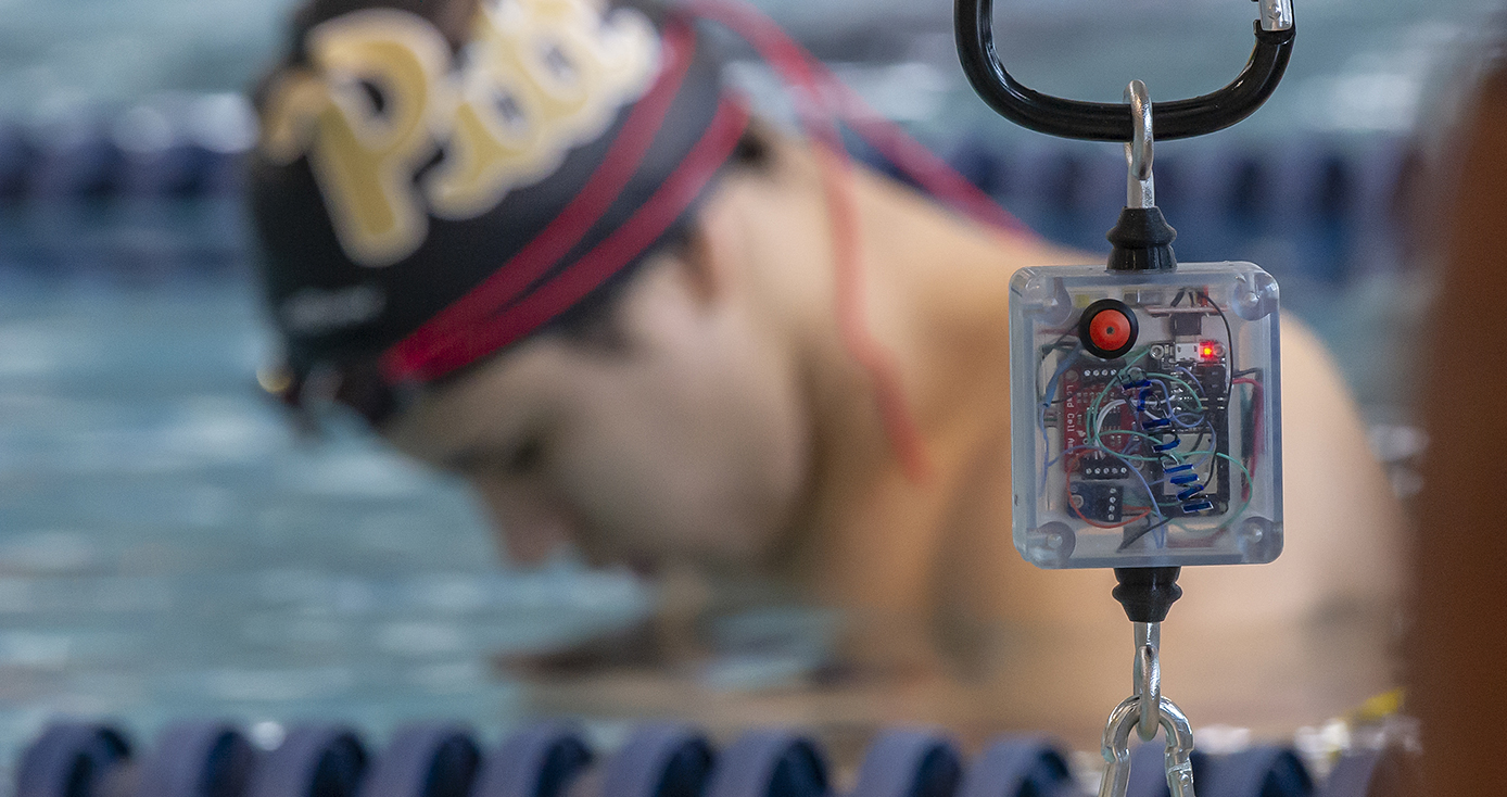 An electronic device hanging by a clip with a swimmer with a Pitt cap on in the background