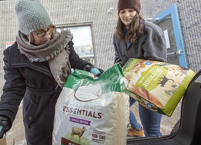two women unloading bags of pet food from a hatchback trunk
