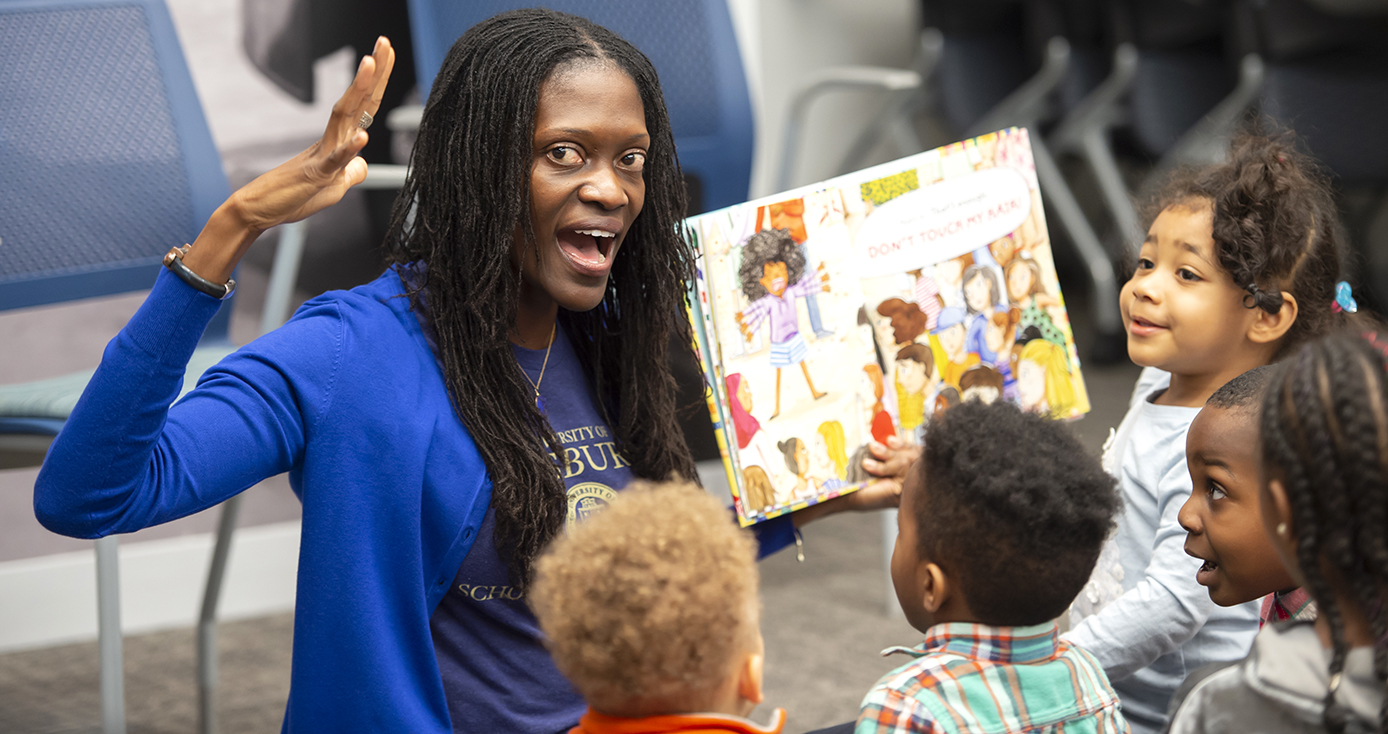 A woman in a blue shirt reading a book to children