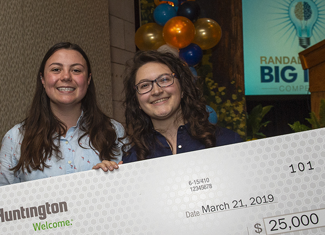Undergrads Lauren Yocum and Emily Siegel holding giant check for $25,000