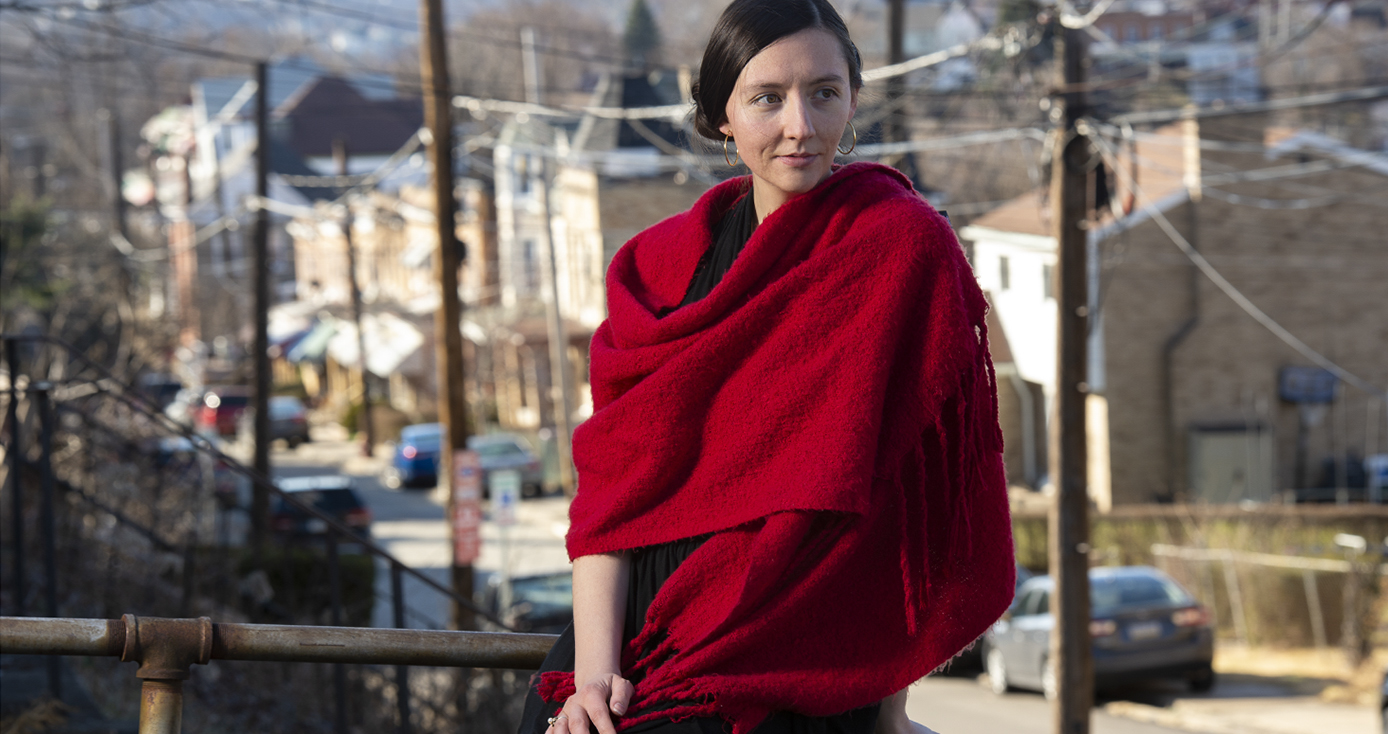 Howell draped in a red scarf, sitting on a porch ledge with a city street in the background