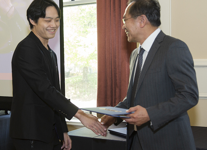 a young man in a black suit shaking hands with an administrator
