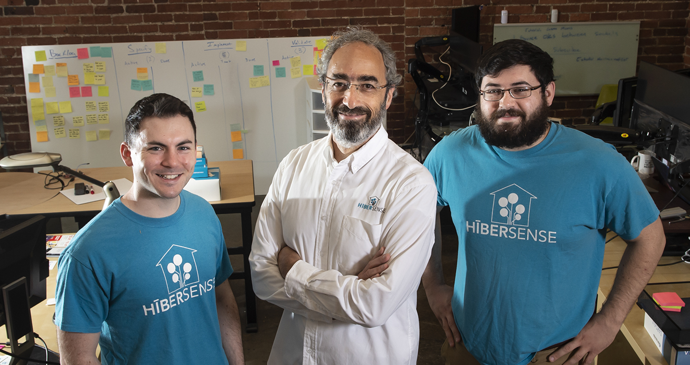 three men standing confidently together, two in Hibersense branded t-shirts