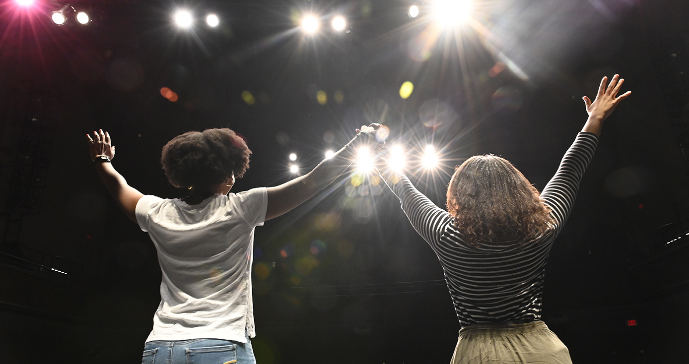 Two people standing side by side, lifting their hands together, facing bright lights