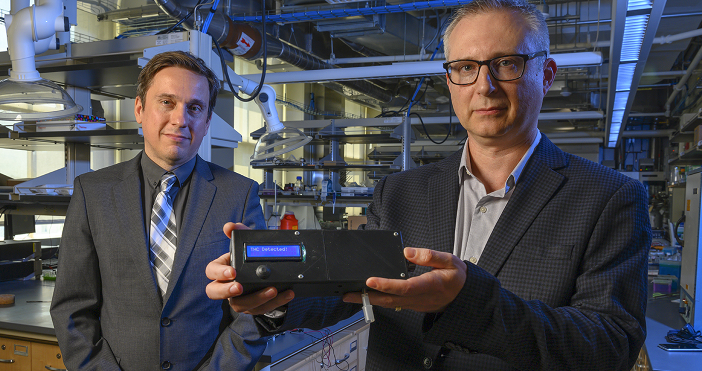 Associate professor of electrical and computer engineering Ervin Sejdic, left, and professor of chemistry Alexander Star show the prototype of the THC Breathalyzer developed using their interdisciplinary research.