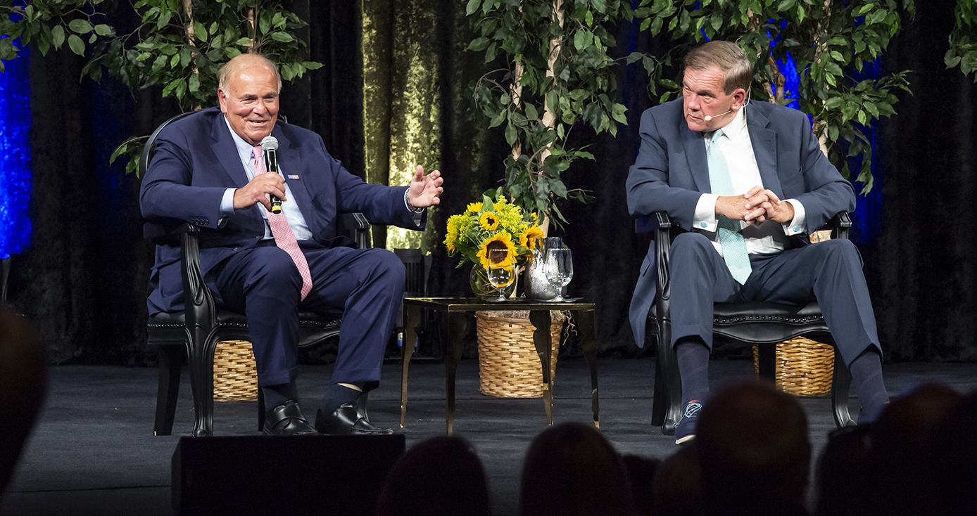 Former Pennsylvania governors Ed Rendell and Tom Ridge on stage with greenery behind them and a table with sunflowers between them. Rendell is speaking into a microphone and gesturing and Ridge's head is turned toward Rendell