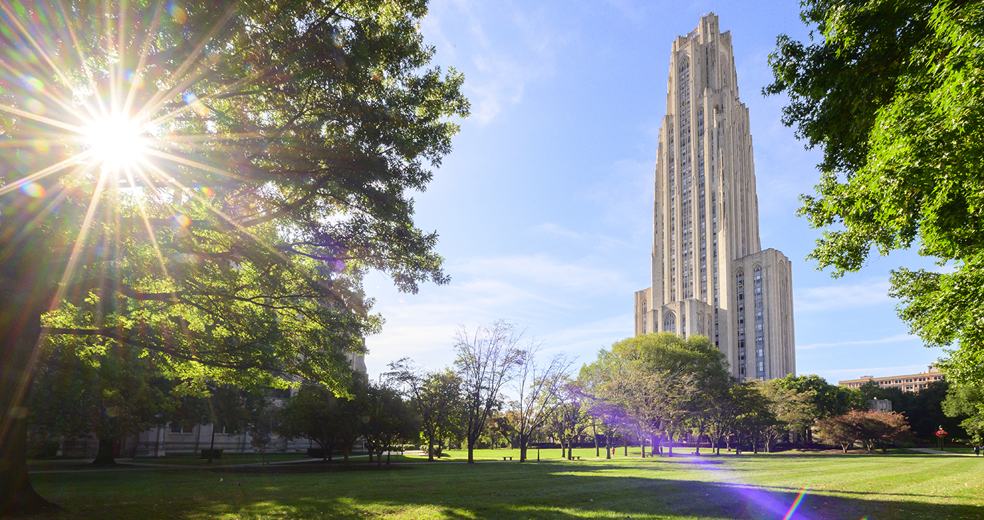 Sun breaking through trees in front of the Cathedral of Learning