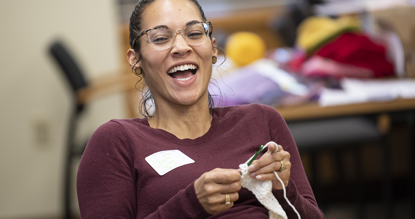 A woman in a maroon long sleeve shirt laughs while knitting