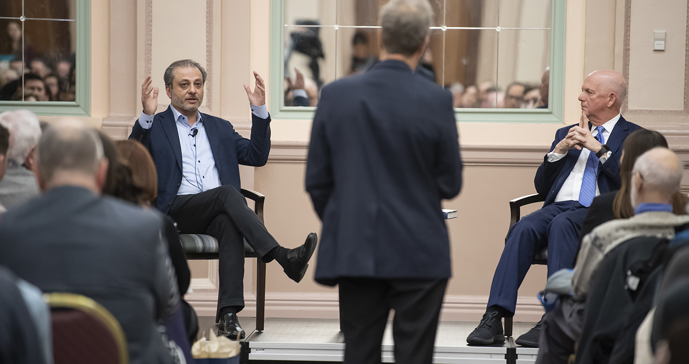 Preet Bharara and David Hickton seated, facing toward an audience; back of audience's heads are visible. Bharara gestures while speaking. Hickton looking toward Bharara.