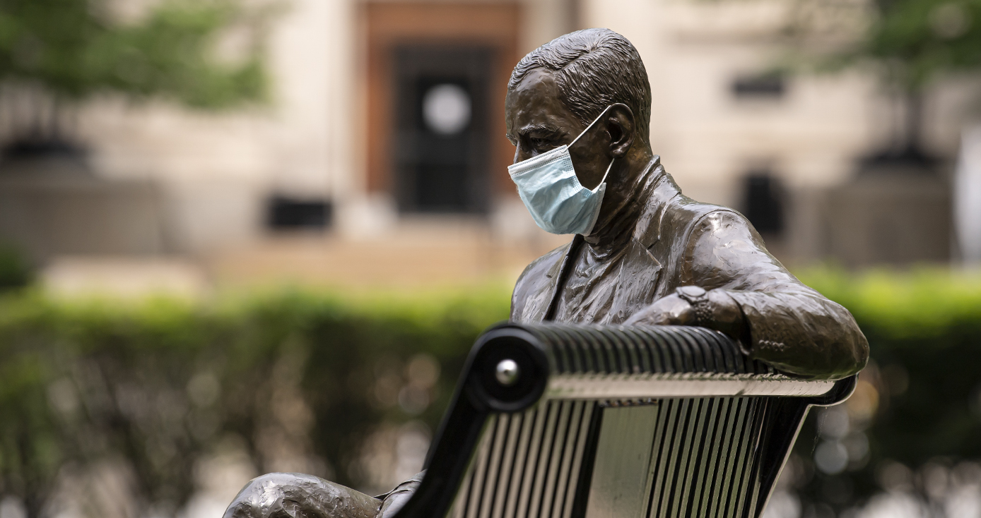 A statue sitting on a bench with a face mask