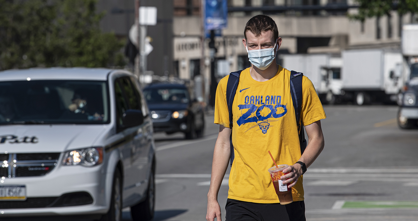A person in an orange t-shirt and face mask walks on campus