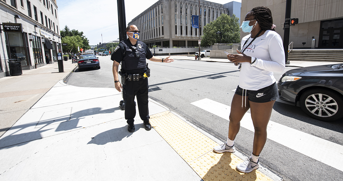 A police officer stands on a sidewalk, speaking to a person in a face mask in a white shirt and black shorts