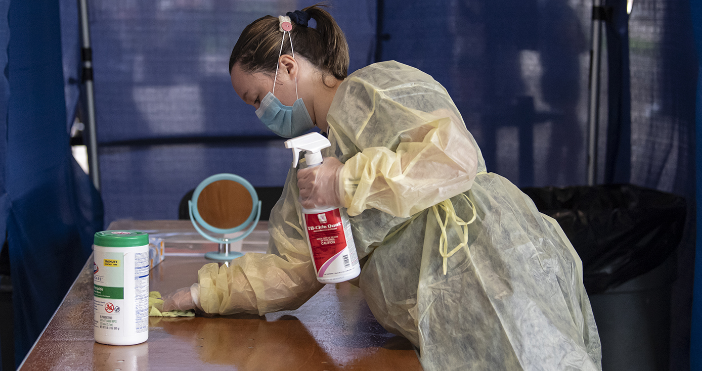 A person in a face mask cleans a testing area