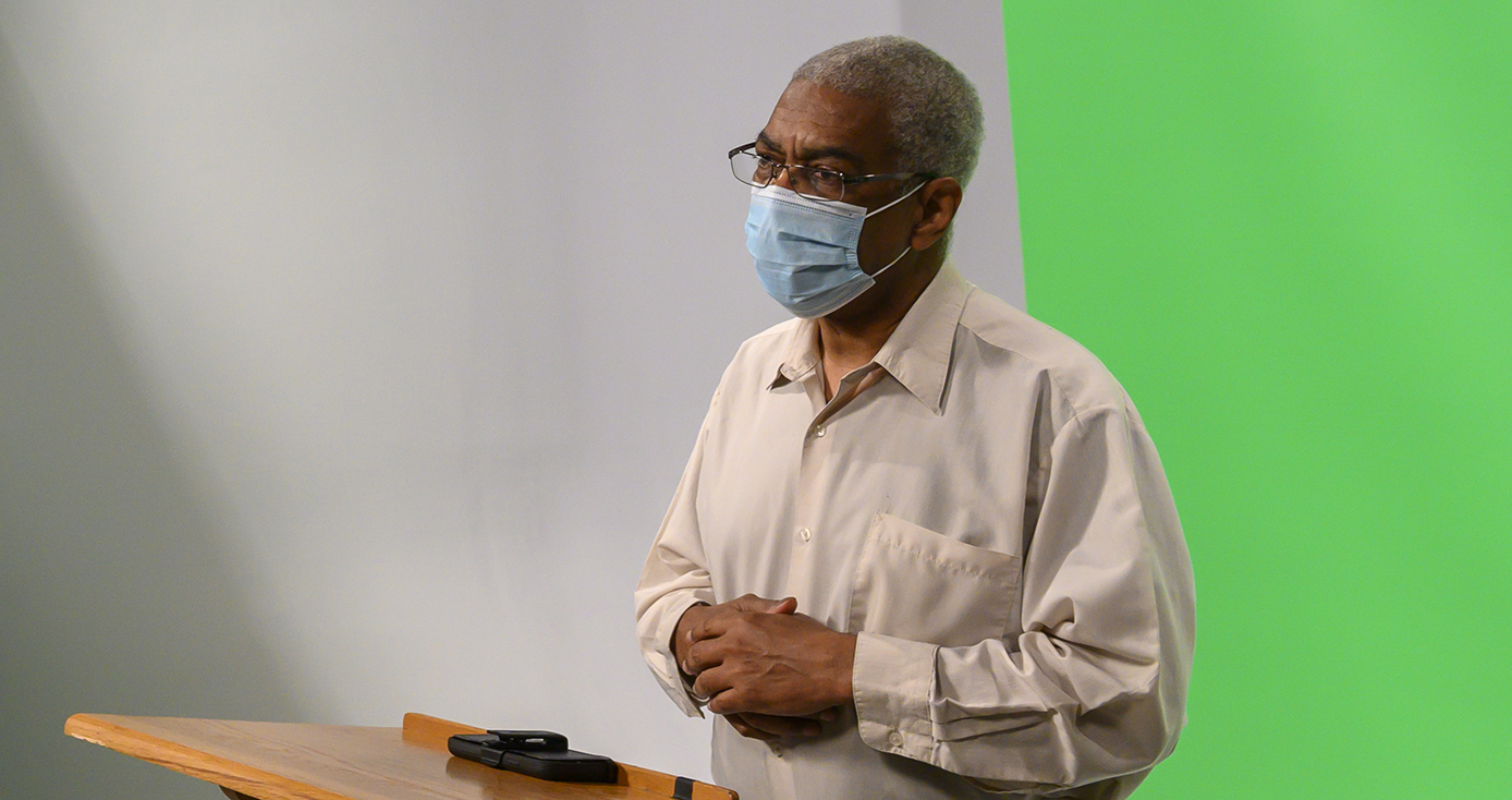 A person in a face mask and tan shirt stands in front of a green screen