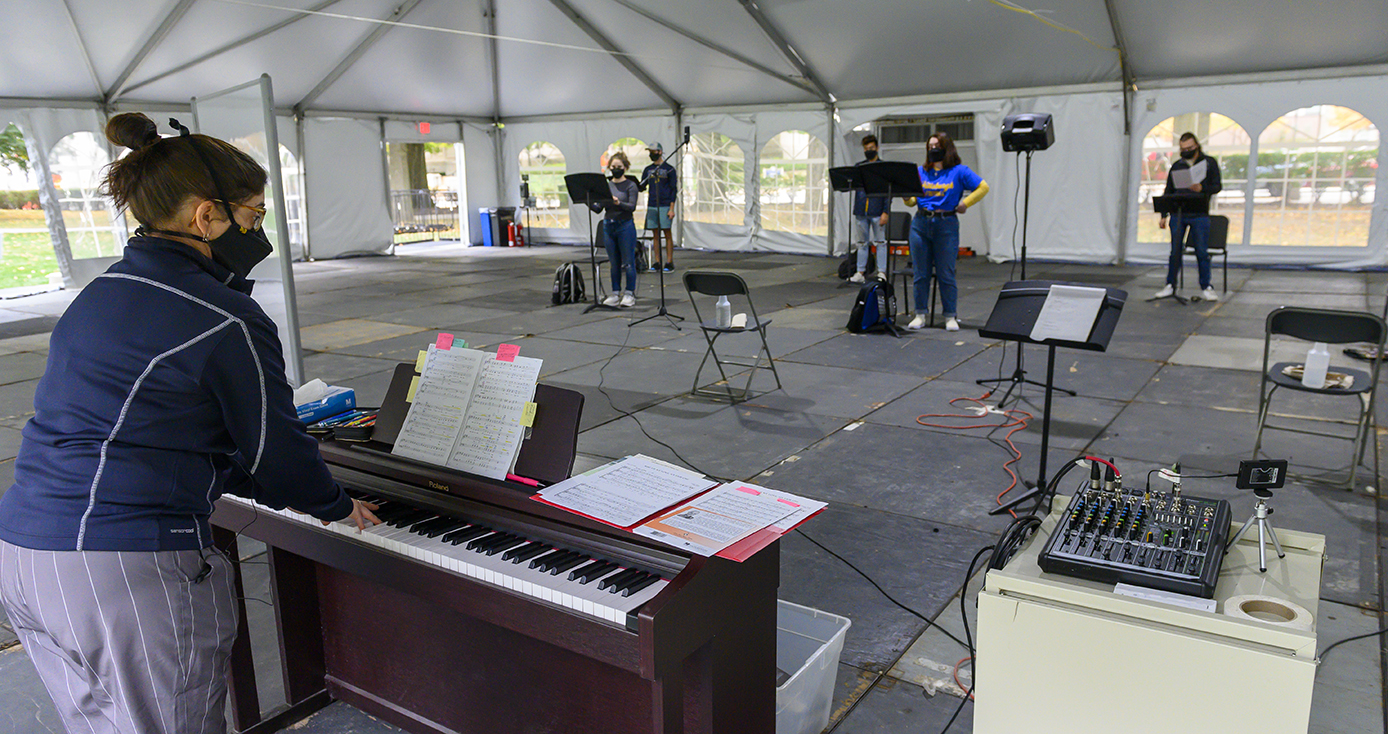 A person plays a piano facing five singers, all inside a tent