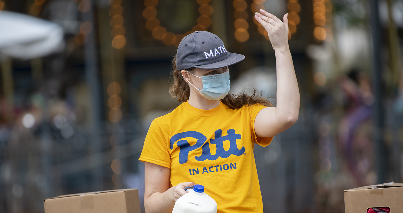 A person in a yellow Pitt shirt, gray hat and face mask waves at someone while holding a gallon of milk