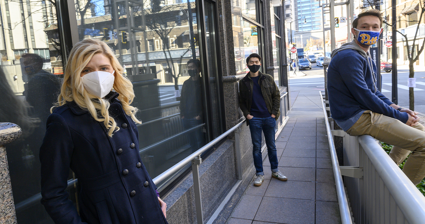 Two people in jackets and face masks on a sidewalk