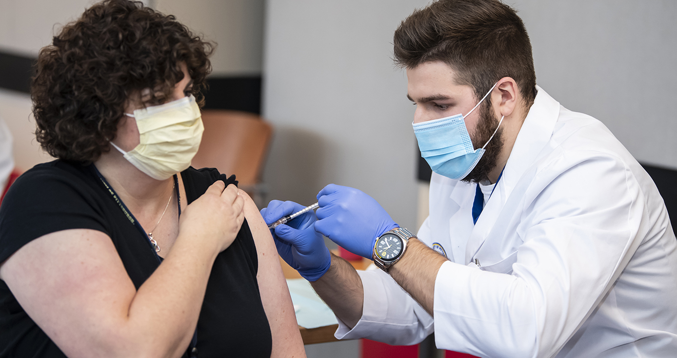 A man in a face mask and white coat and blue gloves administers a vaccine to a person in a yellow face mask and black shirt