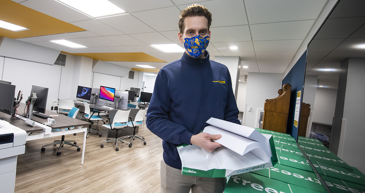 A person in a blue jacket and face mask holds a ream of paper in a classroom