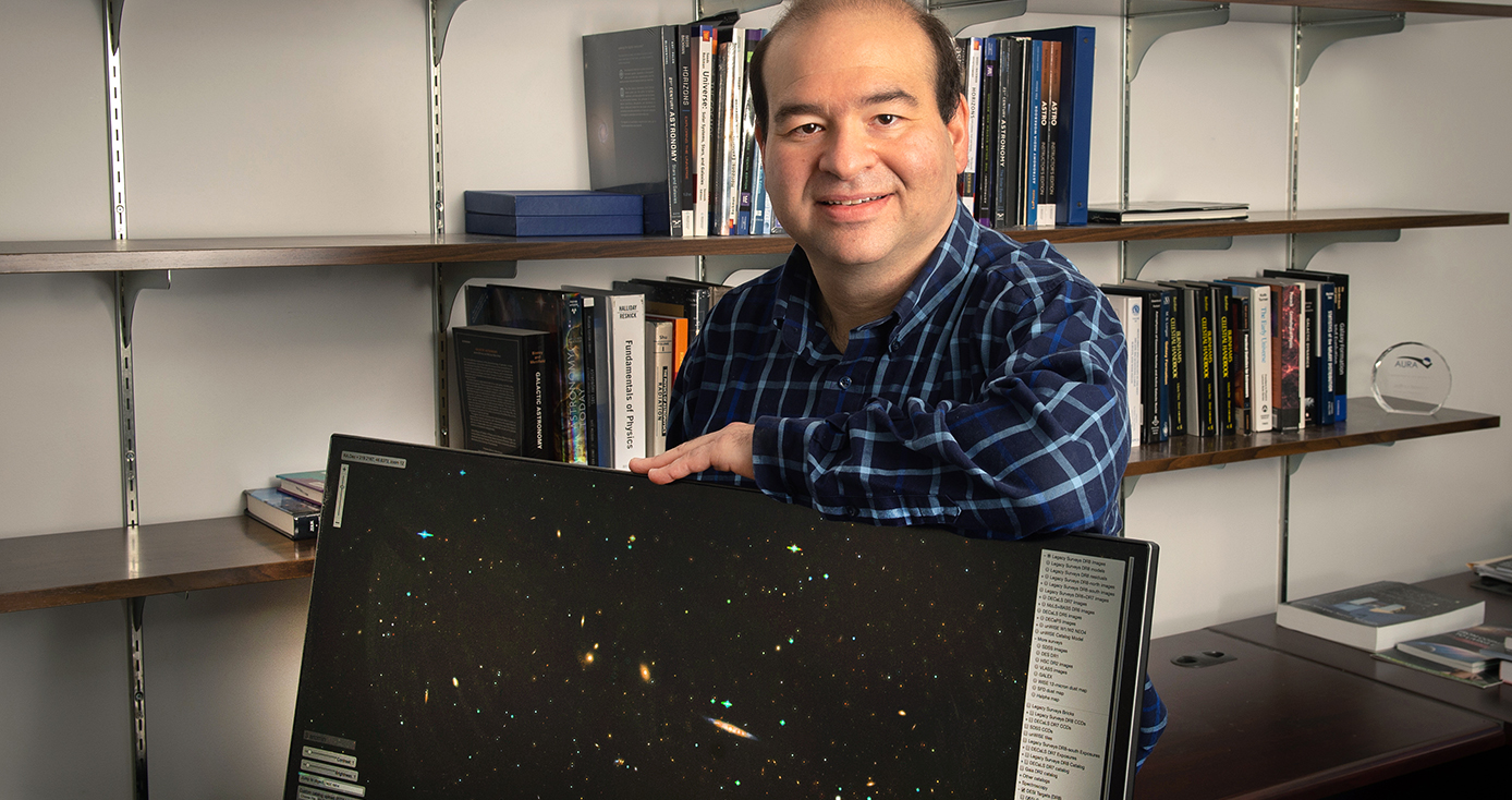 Jeffrey Newman, with a monitor displaying two dimensional stars and galaxies