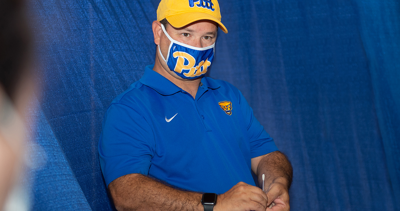 A person in a blue face mask and yellow Pitt hat