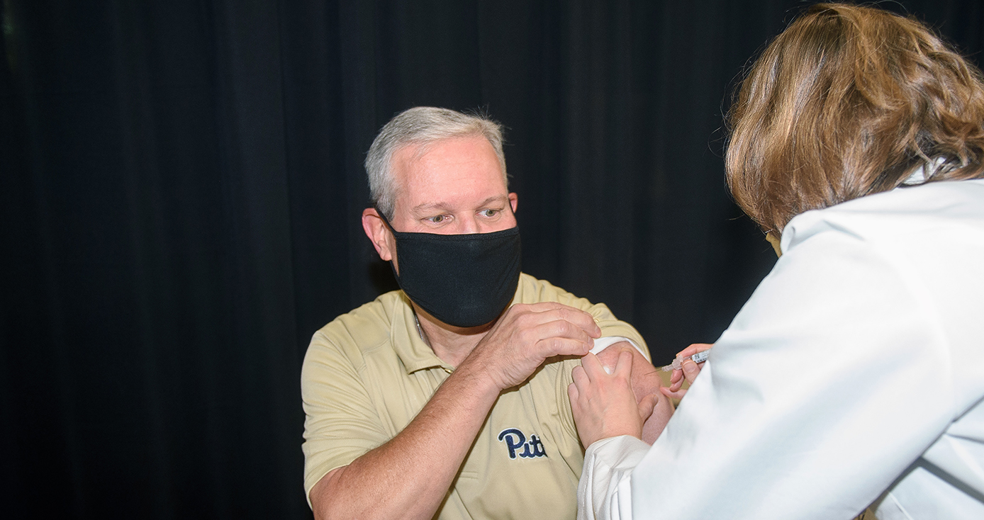 A man in a black face mask and a yellow Pitt shirt receives a shot