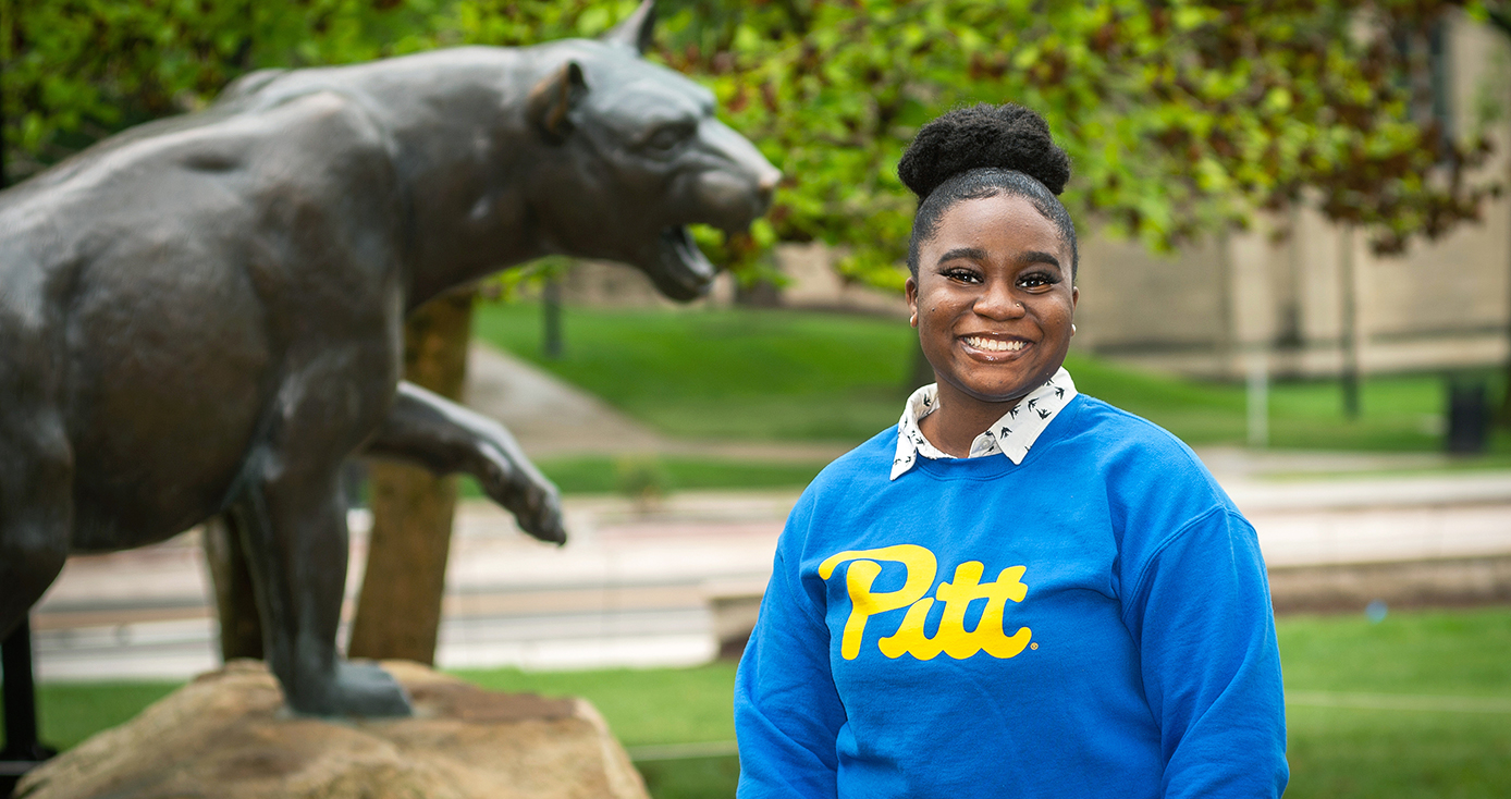 a woman in a blue and gold Pitt shirt smiling broadly in front of a Panther statue
