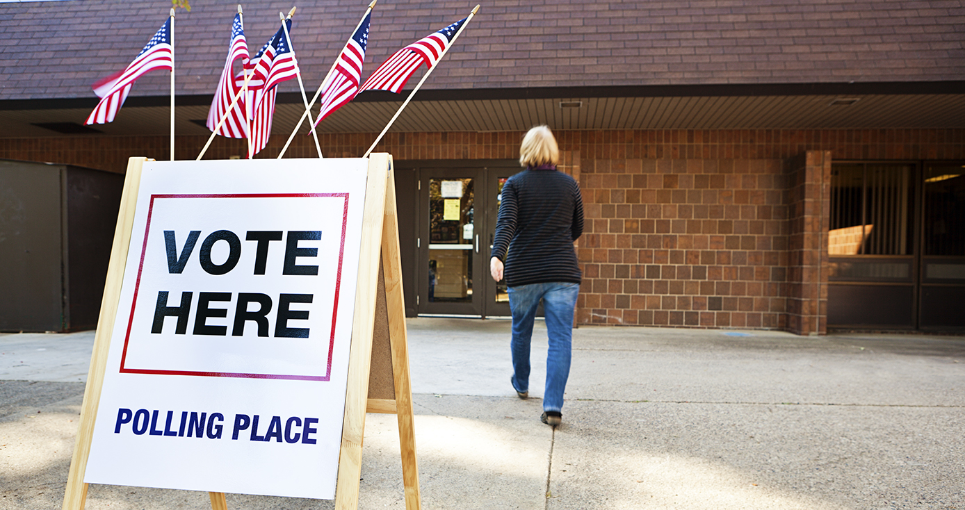 "Brick building in background with person walking toward it a ""Vote Here' sign in the foreground with American flags on top of it"
