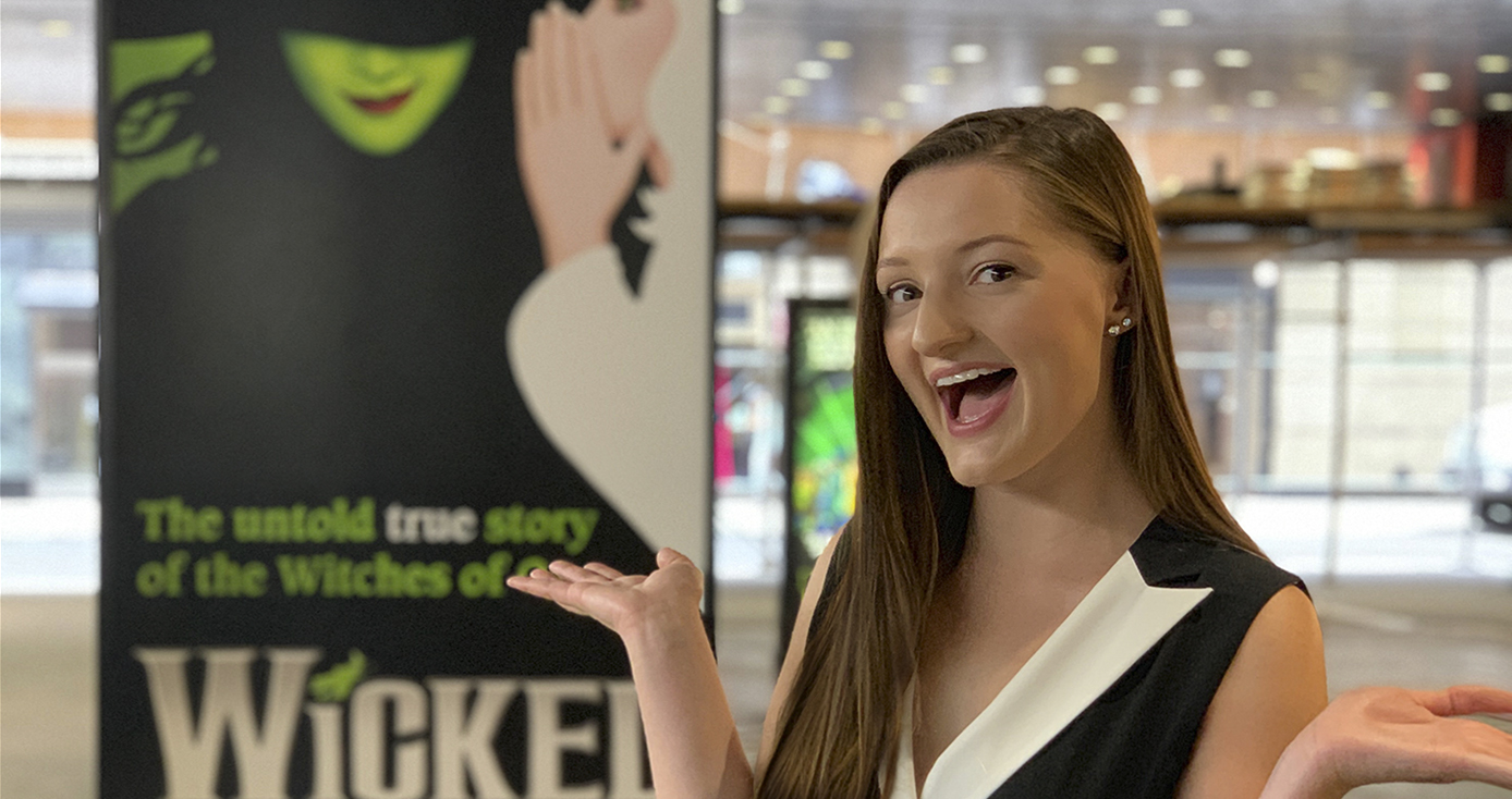 "Rachel Noah in front of a banner for the play ""Wicked"""