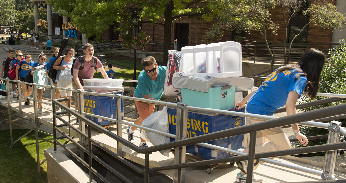 Several students pushing carts of belongings up a ramp