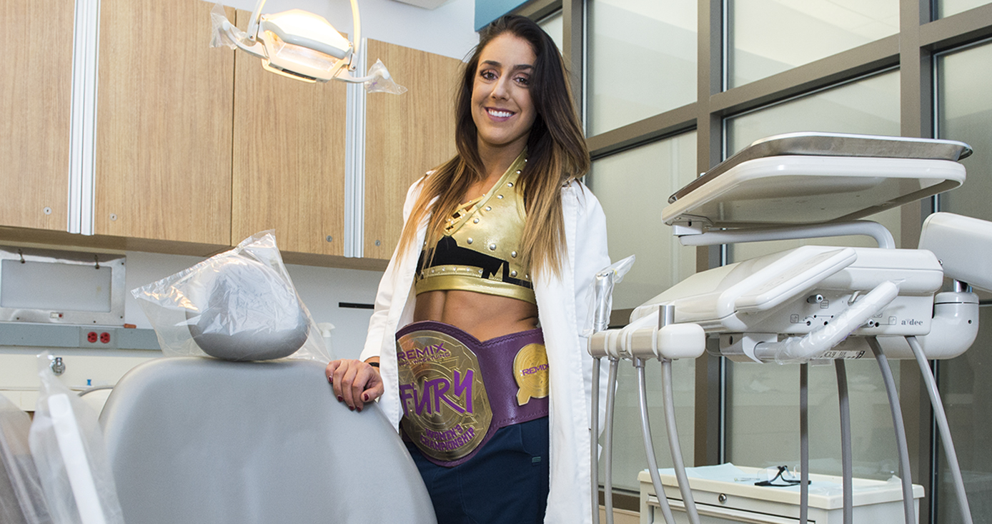 Britt Baker, a woman with long brown hair, wearing a white dentist's coat and a wrestling belt