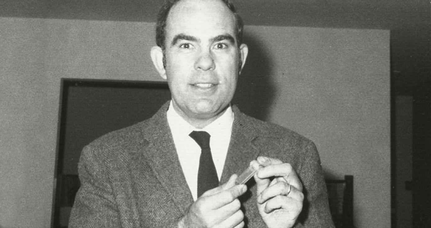a black and white photo of Hapke holding a small tube of moon rocks