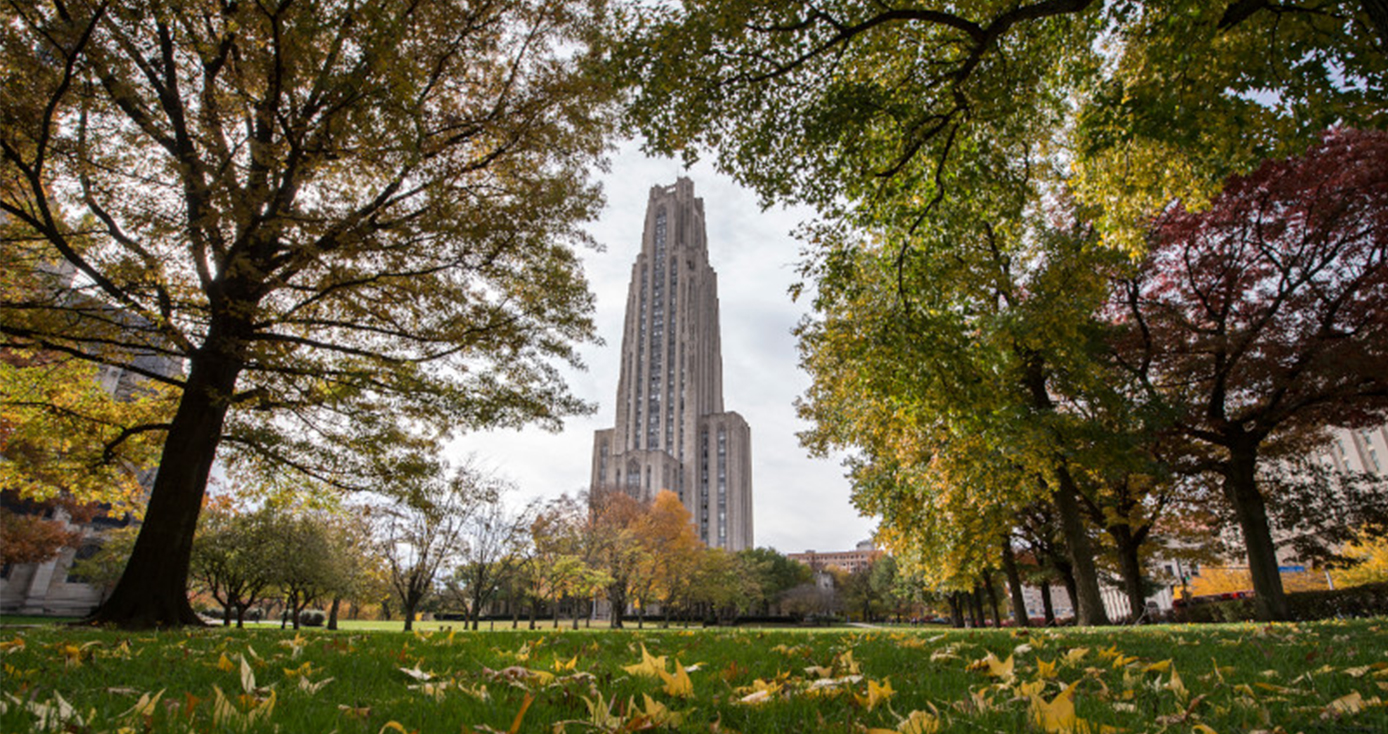 The Cathedral of Learning framed by trees in the fall