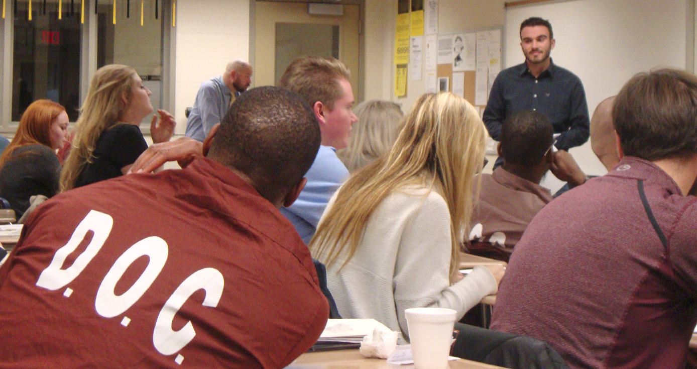 Multiple students with backs facing the camera with professor in background leading class. Student closest to camera has DOC on back of prison uniform.
