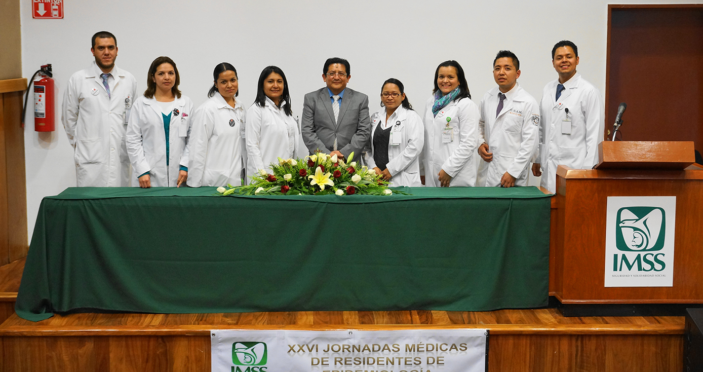 Nine people in white coats stand for a picture in front of a green table with a floral arrangement