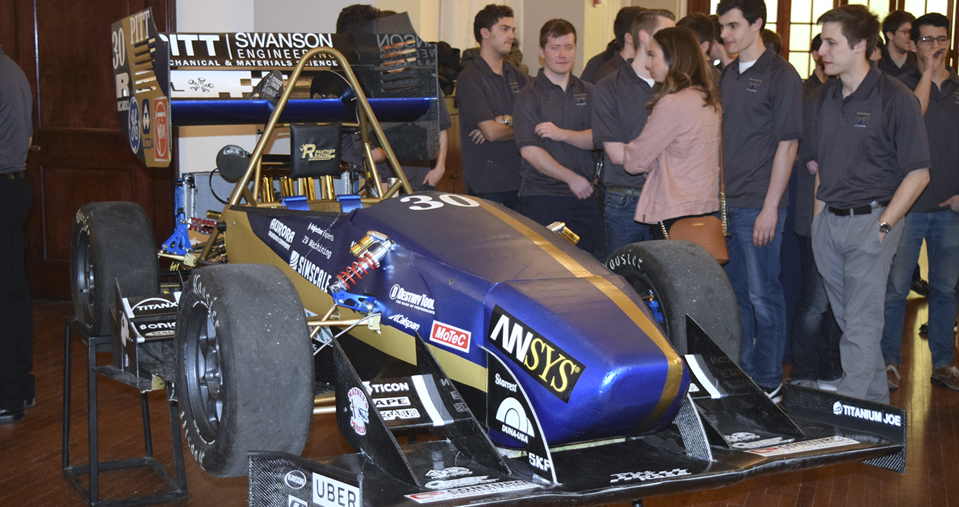 racecar in a blue and gold color theme with a group of students and onlookers standing on the right side of photo