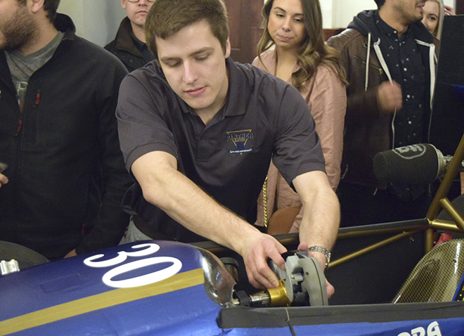 male student working on racecar with a few onlookers in background
