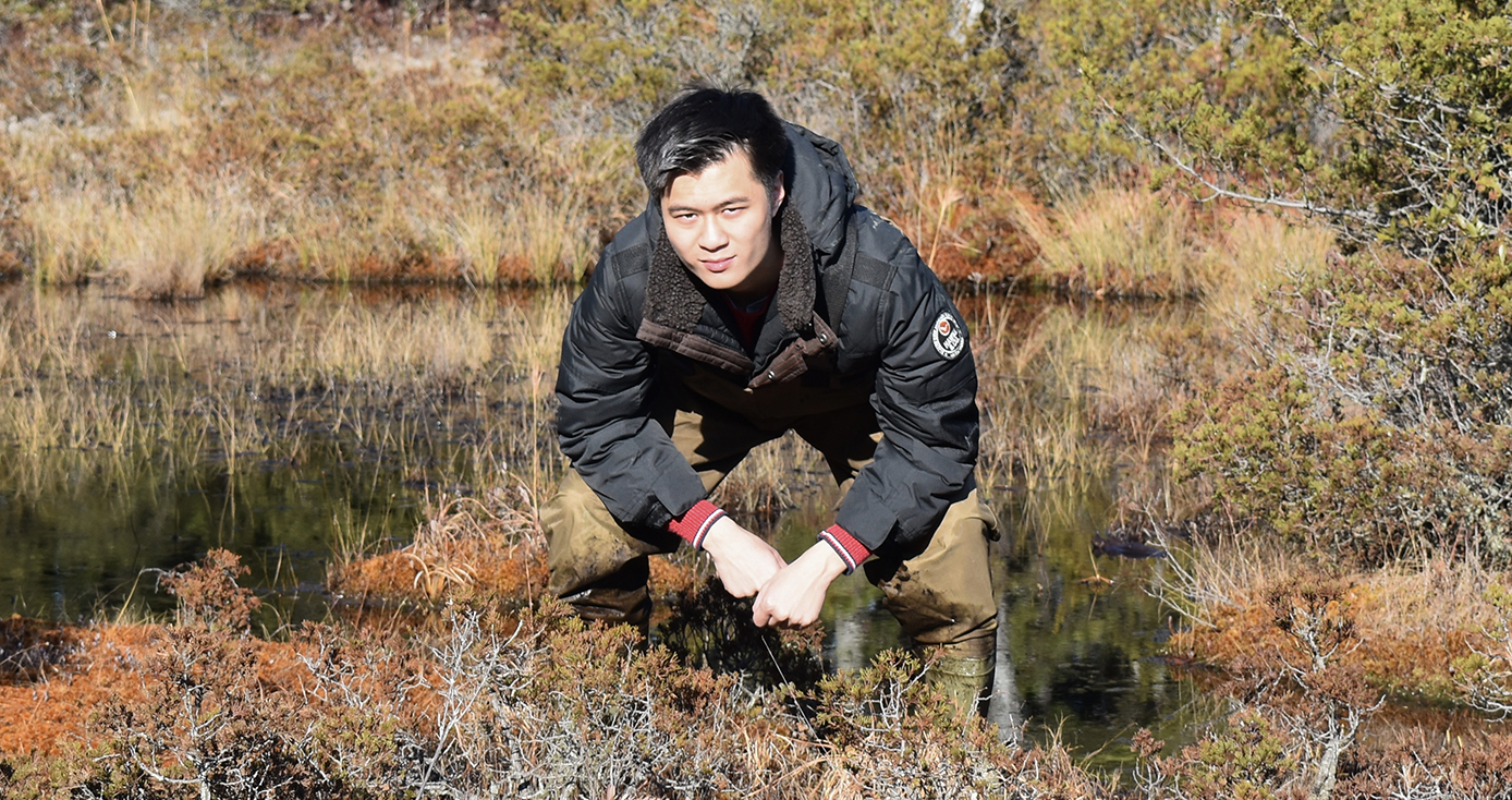 Alvin Liu crouching near a body of water, next to shrubbery