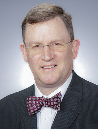 Daniel Hall in a dark suit and red patterned bowtie.